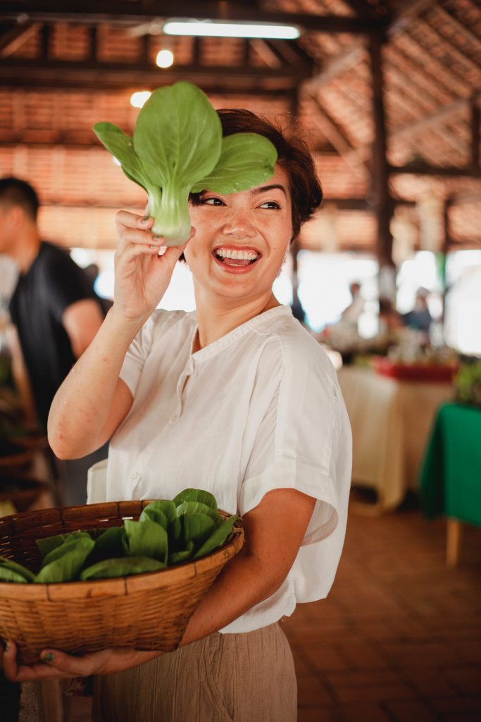 Happy woman holding salad leaf